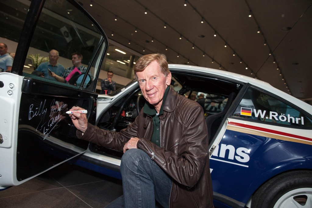 Rallying Legend Walter Rohrl signing the door card of the Porsche he will drive tomorrow...