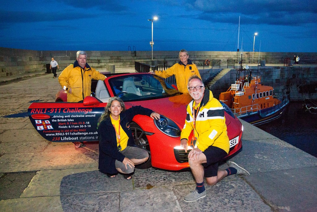 Belinda & James Richardson (front) with Donaghadee RNLI crew members John Petrie (left) and Nikki Butler (right) pictured with the RNLI Porsche 911 Challenge car, Splash, and the Donaghadee RNLI Trent-class lifeboat 'Saxon' 14-36.